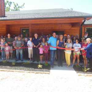 Group picture of ribbon cutting ceremony for House of Healing bunkhouse